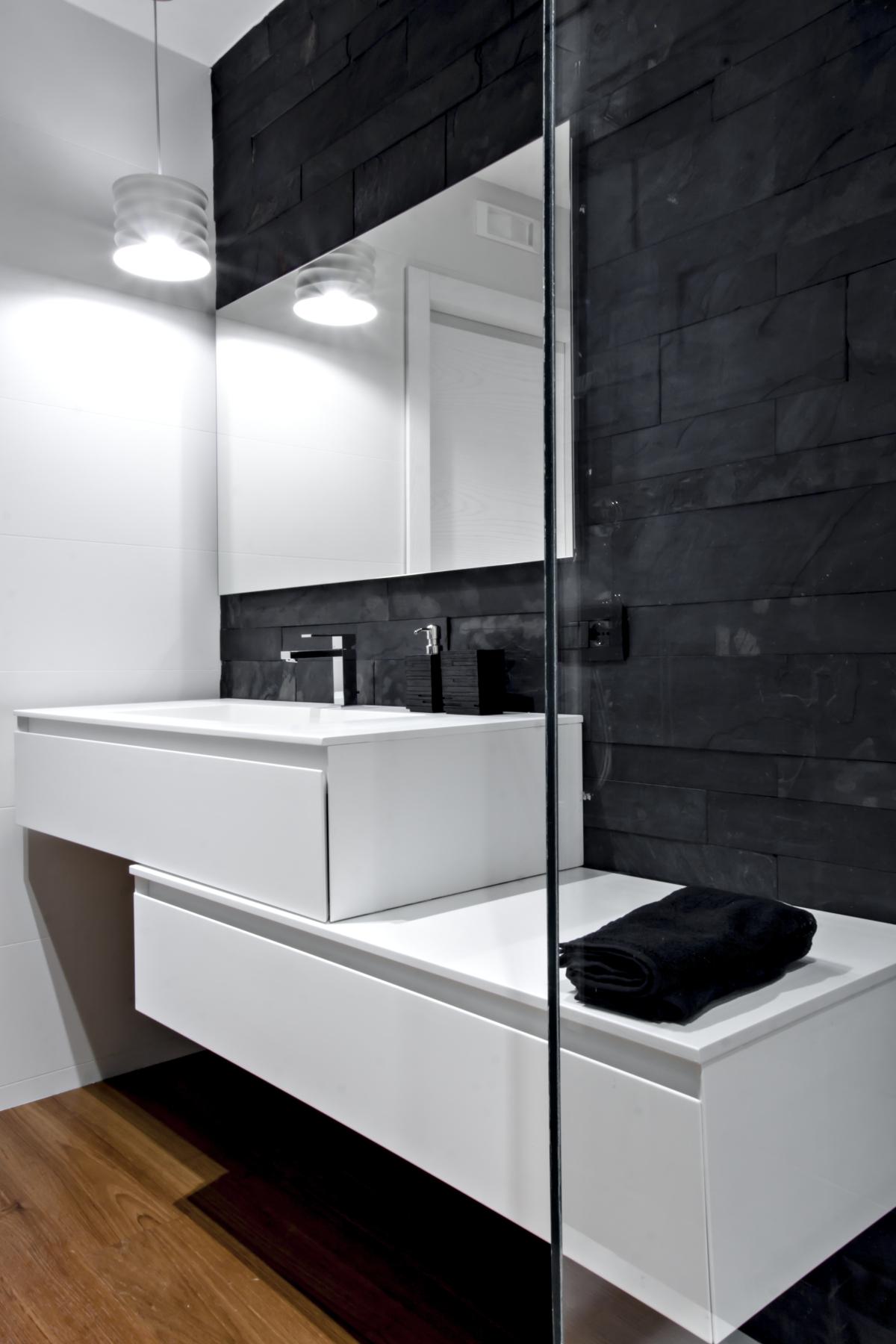 mur de salle de bains recouverte d'ardoise noire et de meubles de l'essence et de la pierre. Parquet Burmese teck.